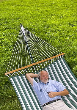 Elderly gentleman lying in a hammock and listening to music