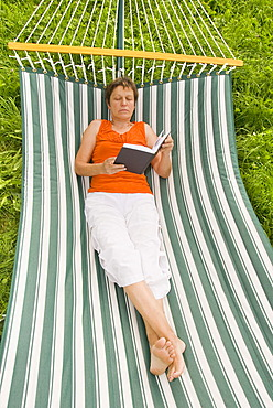 Senior woman with book lying in a hammock