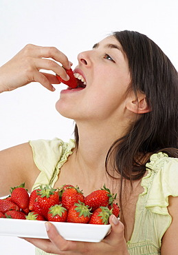 Young woman eats strawberries