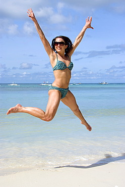 Young woman jumping on the beach