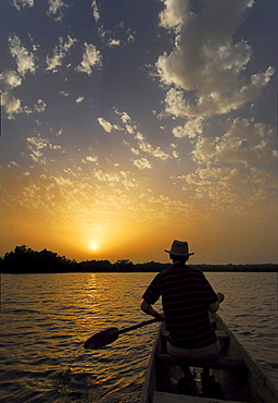 Tourist canoing on the River Gambia und enjoying the sunset, near Tumani Tenda, The Gambia, Africa
