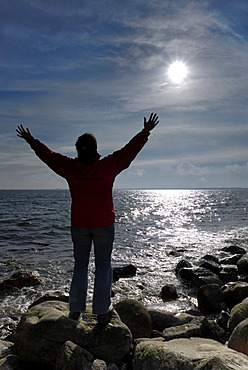 Woman spreads her arms and enjoys the sun, Kiel Bay, Schleswig-Holstein, Germany