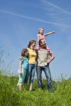 Family standing relaxed in a flower meadow