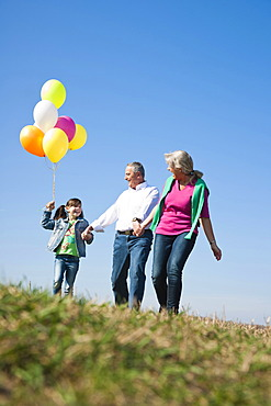 Girls holding balloons in her hand while walking with her grandparents across a meadow