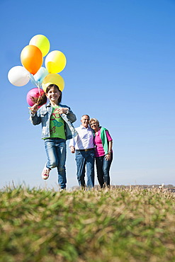 Girls holding balloons in her hand while running across a meadow in front of her grandparents