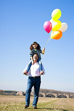 Girl holding many colourful balloons in her hand while sitting on her grandfather's shoulders
