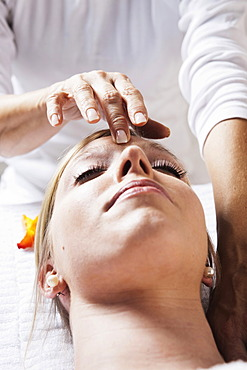 Young woman being treated by a therapist on her head and upper torso