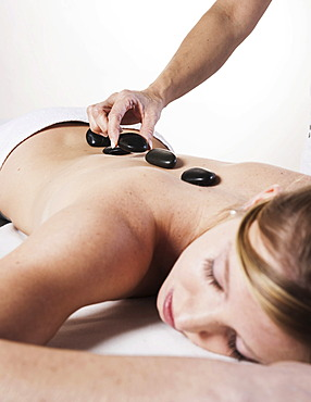 Young woman being treated with hot stones, hot stone massage