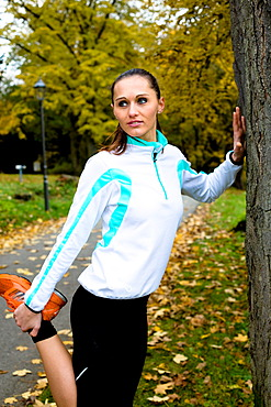 Young woman warming up as preparation for jogging