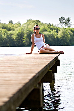 Young woman sitting on jetty at lakeside