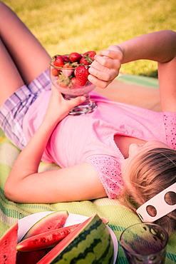 Girl eating strawberries in the garden
