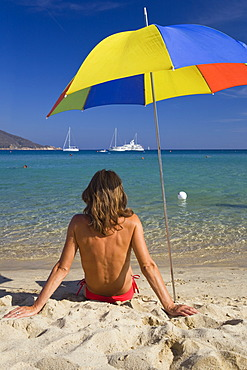 Woman sitting on the beach of Marina di Campo, Island of Elba, Tuscany, Italy, Mediterranean Sea, Europe
