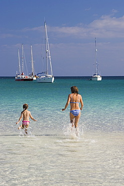 Woman and child running in water at Cala Brandinchi Beach eastcoast Sardinia Italy