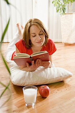 Woman laying on a parquet floor reading a book