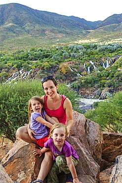 Mother with two girls sitting on rocks in green landscape, behind Epupa Falls, Kunene, Kunene region, Namibia, Africa