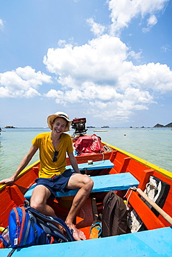 Young man sitting in longtail boat, turquoise sea, Koh Tao, Gulf of Thailand, Thailand, Asia