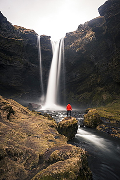 Man in red jacket in front of Kvernufoss waterfall in a gorge, dramatic atmosphere, time exposure, near Skógafoss, Southurland, Iceland, Europe