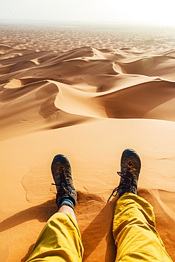 Legs with hiking boots in the sand, sand dune, desert, Erg Chebbi, Merzouga, Sahara, Morocco, Africa