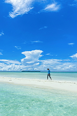 Tourist walking on a sand strip at low tide, Rock Islands, Palau, Oceania