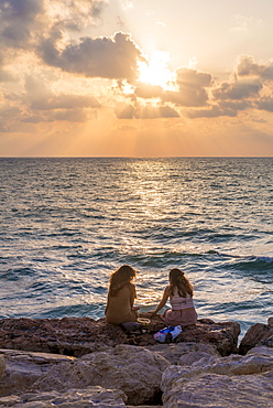 Two women sitting on rocks at sunset overlooking the sea, Tel Aviv, Israel, Asia