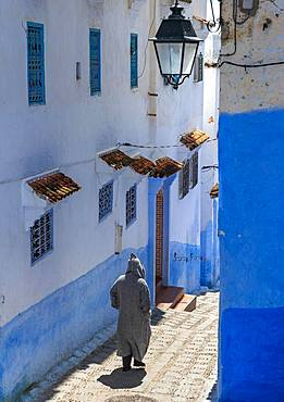 Local in Djellaba, stairs through narrow lane, blue houses, Medina of Chefchaouen, Chaouen, Tanger-Tetouan, Morocco, Africa