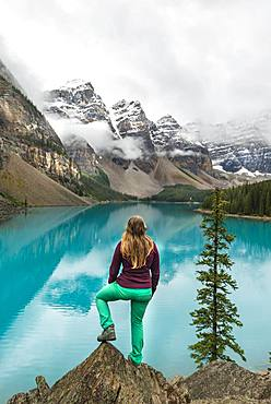 Young woman standing in front of a lake looking into mountain scenery, clouds hanging between mountain peaks, reflection in turquoise lake, Moraine Lake, Valley of the Ten Peaks, Rocky Mountains, Banff National Park, Province of Alberta, Canada, North America