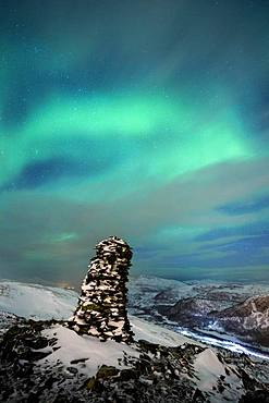 Northern Lights (aurora borealis), with stone figure in cloudy sky on Jamnfjellet, Tromsoe, Norway, Europe
