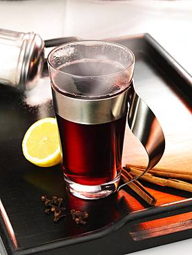 Hot mulled wine on dark tray, lemon, cinnamon sticks, cloves and sugar, Germany, Europe