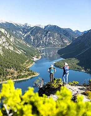 Two hikers look into the distance over the Lake Plansee, surrounded by mountains, Schoenjoechl, Plansee, Tyrol, Austria at the back.
