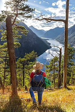 Young hiker at the view from Schoenjoechl, Lake Plansee surrounded by mountains, Tyrol, Austria, Europe