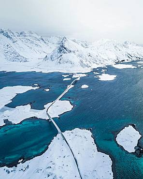 Snow-covered landscape at the fjord with Fredvang bridges, drone shot, Lofoten, Norway, Europe