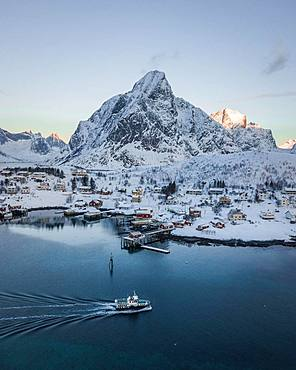 Place Reine voe snowy mountains with passenger boat, drone shot, Lofoten, Norway, Europe