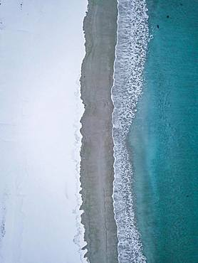 Haukland beach from above, turquoise sea water borders on snow surface, drone shot, Lofoten, Norway, Europe