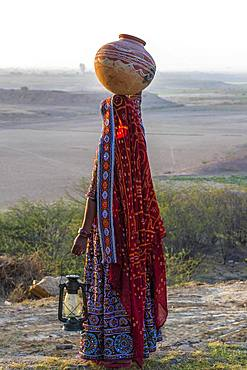 Ahir woman in traditional colorful clothes carrying water in a clay jug on her head, Great Rann of Kutch, Gujarat, India, Asia