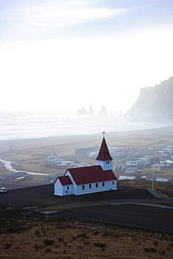 Small church with red roof, behind it the village Vik and the rocks of Reynisfjara, Sudurland, South Iceland, Iceland, Europe