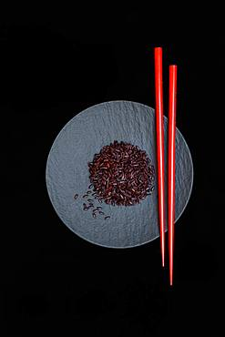 Black rice with red chopsticks on plate, cooked, Germany, Europe