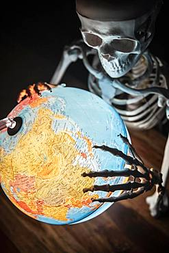 Skeleton with bony hand on globe, symbolic image of war and environmental catastrophe, Germany, Europe