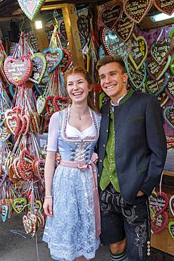 Young couple in traditional traditional traditional traditional traditional traditional traditional traditional traditional traditional costume in front of gingerbread hearts, gingerbread stand, Wiesn, Wiesn, Oktoberfest, Munich, Upper Bavaria, Bavaria, Germany, Europe