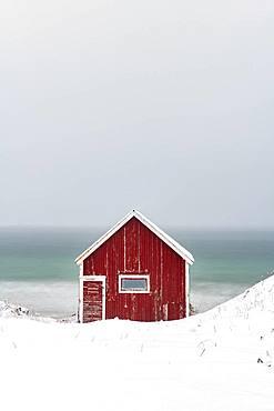 Rorbuer fishing hut on the beach in the snow, Ramberg, Flakstadoya, Lofoten, Norway, Europe