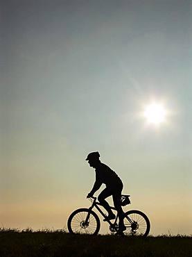 Cyclist on bike tour with mountain bike, silhouette against the light, Salzkammergut, Upper Austria, Austria, Europe