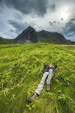 Woman lies pleasurably in a meadow in front of threatening mountain range, Skagsanden, Flakstad, Lofoten, Nordland, Norway, Europe