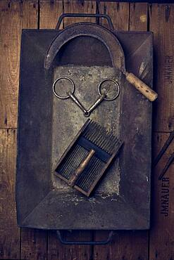 Rural tools, sickle, snaffle, blueberry grater, in an embers tub
