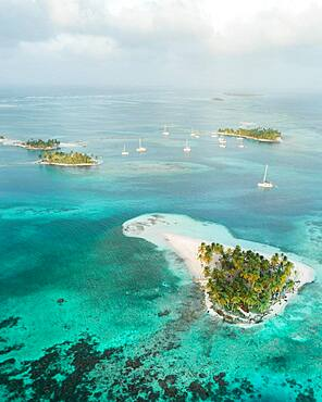 Aerial view, sailing boats between several small tropical palm islands, San Blas Islands