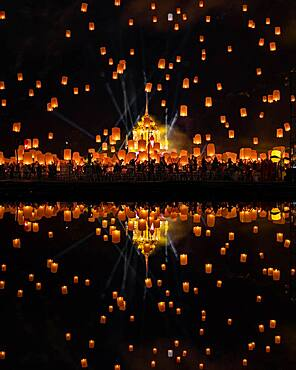 Yi Peng Festival with rising lanterns and a reflection in the lake, Chiang Mai, Thailand, Asia