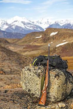 Rifle leaning against rock, barren landscape, protection from polar bears, east coast Greenland, Denmark, Europe