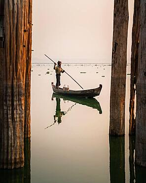 Fisherman stands with boat on Taung Tha Man Lake for sunrise between the posts of the U-leg bridge, reflection in the water, Thaung Tha Man Lake, Mandalay, Myanmar, Asia