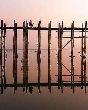 Buddhist monks walk across the U-leg bridge in red robes as the sun rises, Mandalay, Myanmar, Asia