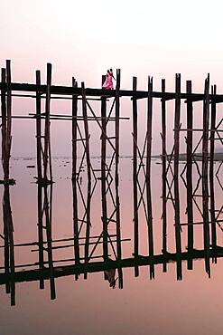 Buddhist monks walk across the U-leg bridge in pink robes as the sun rises, Mandalay, Myanmar, Asia