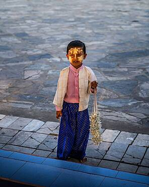 Small boy with yellow face painting, sandalwood, in the Kuthodaw Pagoda, Mandalay, Myanmar, Asia