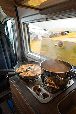 Spaghetti with creamy cream sauce cooked on gas stove in Campervan, Moskenes Camping, Lofoten, Norway, Europe